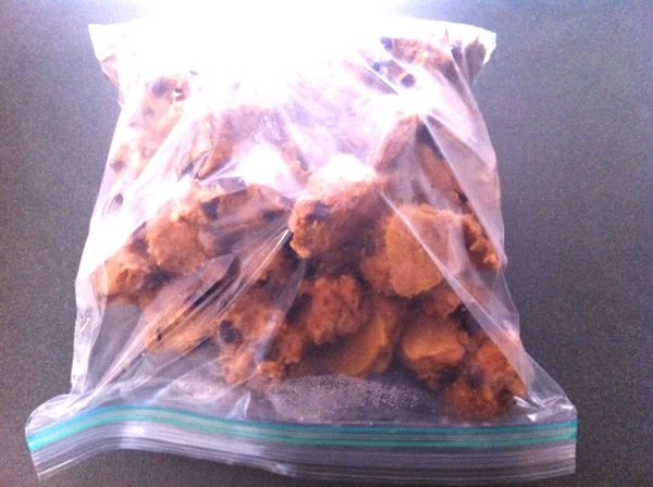 Frozen raw cookie dough portions placed in a plastic freezer bag.