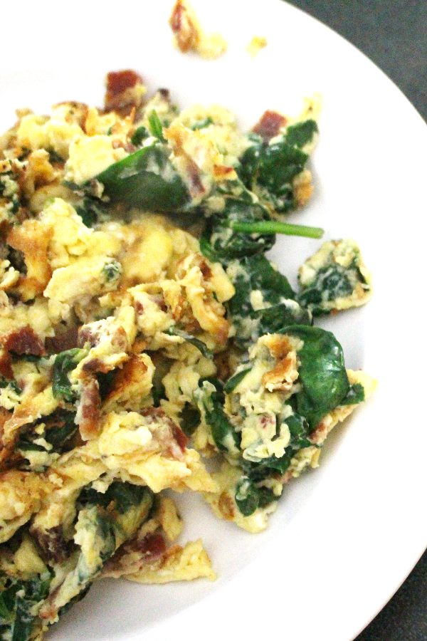 Scrambled eggs with cheese, bacon, and spinach on a white plate