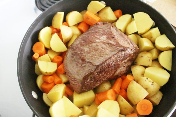 pot roast and vegetables in roasting pan