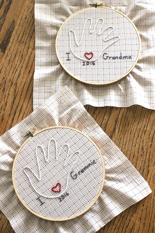 child's handprint hand embroidered on fabric and displayed in an embroidery hoop