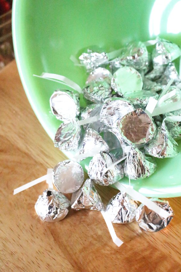 homemade chocolate kisses wrapped in silver foil in a green vintage bowl