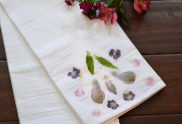 naturally dyed tea towel with flowers on floor