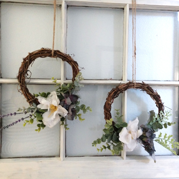spring wreaths hanging from an upcycled winder frame