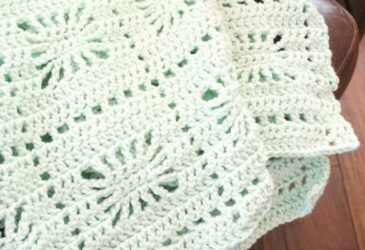 Close up of spiderweb crochet baby blanket in mint green over the arm of a chair
