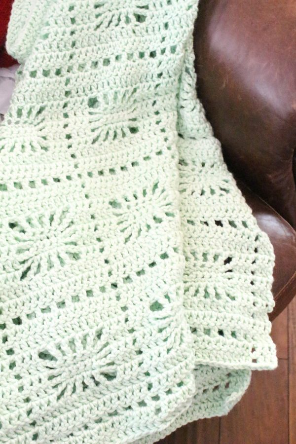 Spiderweb crochet baby blanket in mint green over the arm of a chair