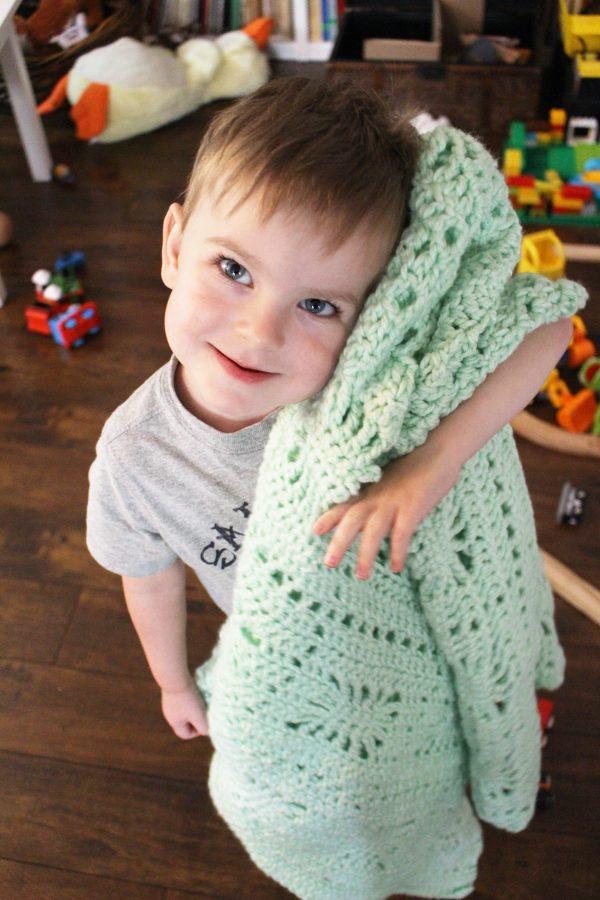 Child holding handmade crochet baby blanket