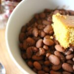homemade southern pinto beans in bowl with cornbread on top