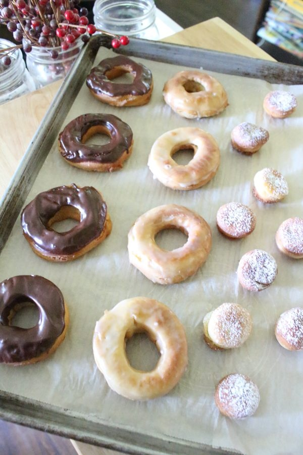 einkorn yeast donuts chocolate glazed and powdered sugar varieties on a baking sheet