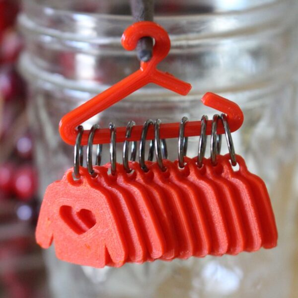 Sweater Knitting Markers hanging from a red coat hanger