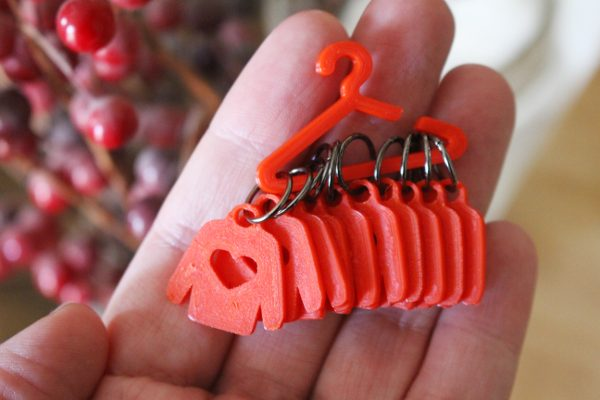 Sweater Knitting Markers hanging from a red coat hanger in a woman's hand