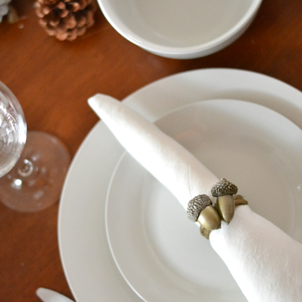 handmade acorn napkin ring sitting on a plate on a table