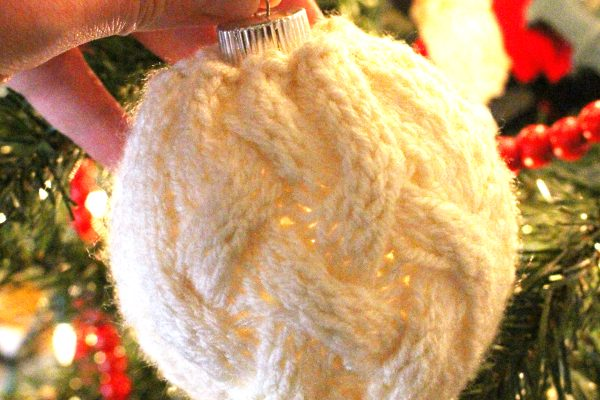 Cable Knit Christmas Ornament in front of Christmas tree with lights