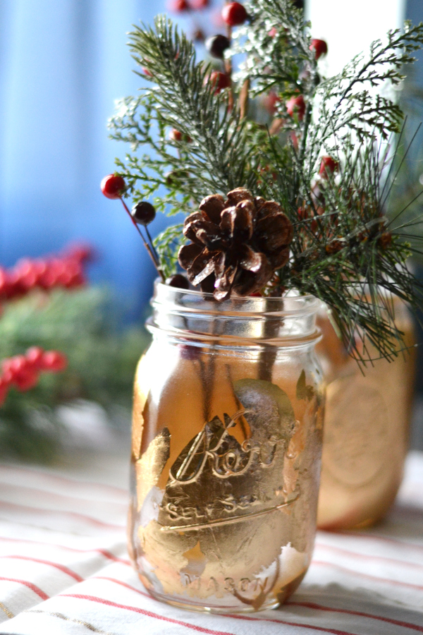 mason jar vase filled with pine sitting on a table