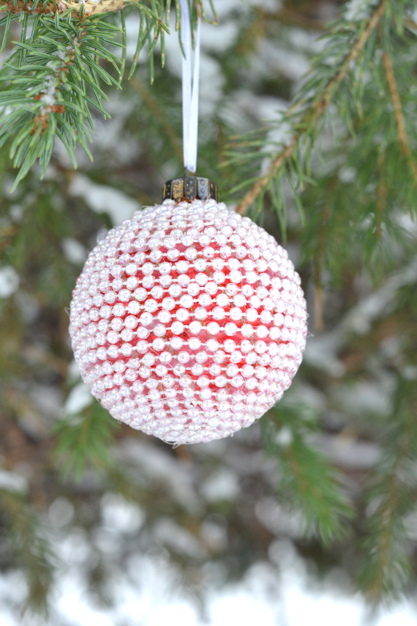 pearl DIY ornament hanging in a pine tree
