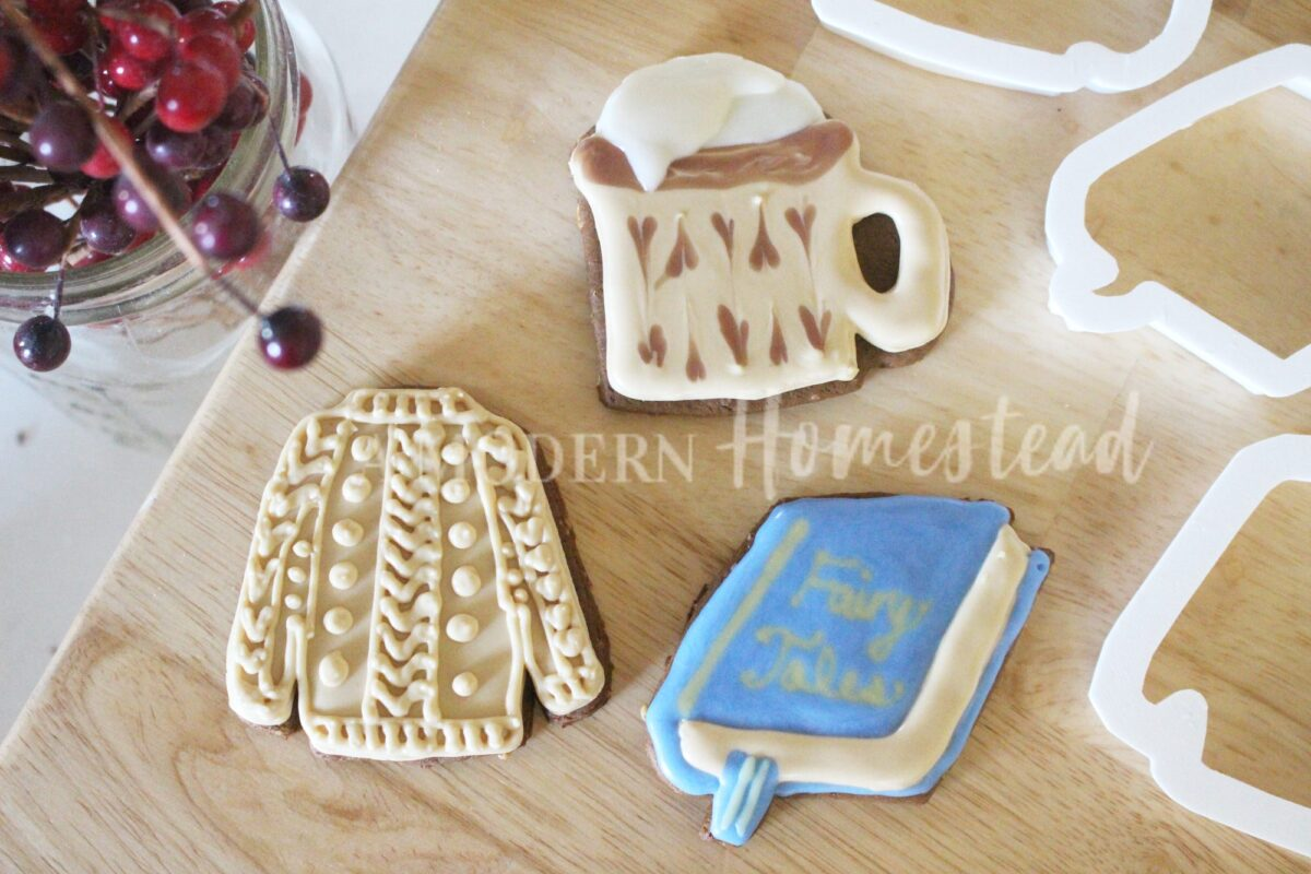 Cozy cookies in the shape of a sweater, camp mug, and book with bookmark