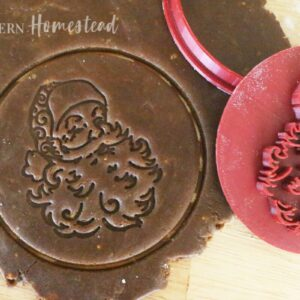 Vintage santa claus cookie cutter and cookie stamp pressed into gingerbread cookie dough
