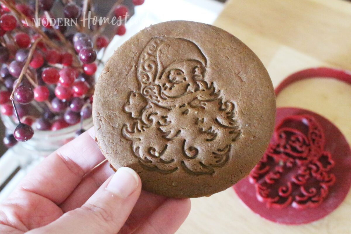 Vintage santa claus cookie cutter and cookie stamp shown on finished gingerbread cookie