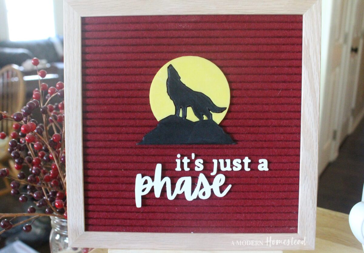 Letter Board icon set of black wolf in front of yellow full moon on red letter board with the words it's just a phase in white
