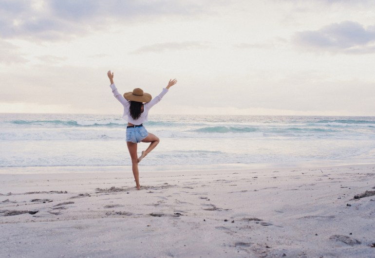 Woman practicing yoga and mindfulness on beach