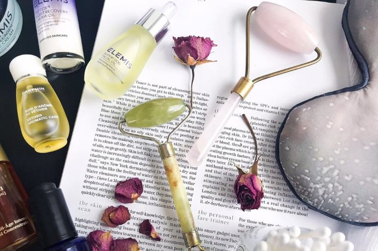 crystal facial rollers with skincare products and roses around them.