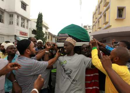 muslim men carrying a casket draped with green cloth