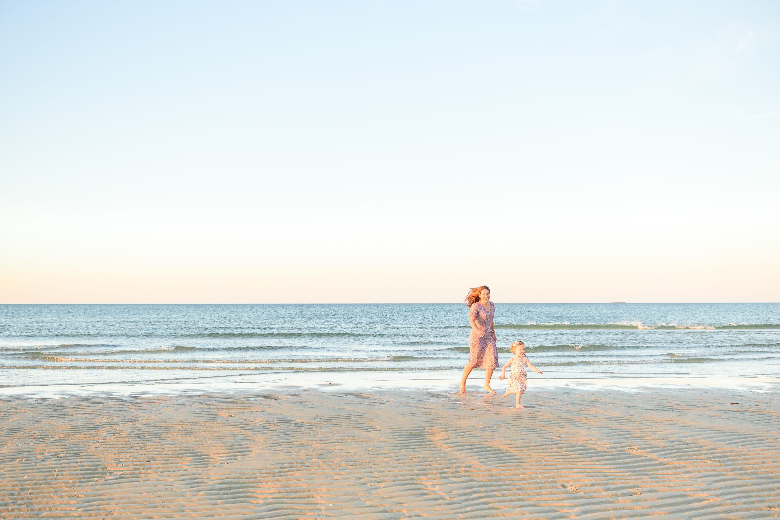 mother and daughter running at the beach during motherhood session