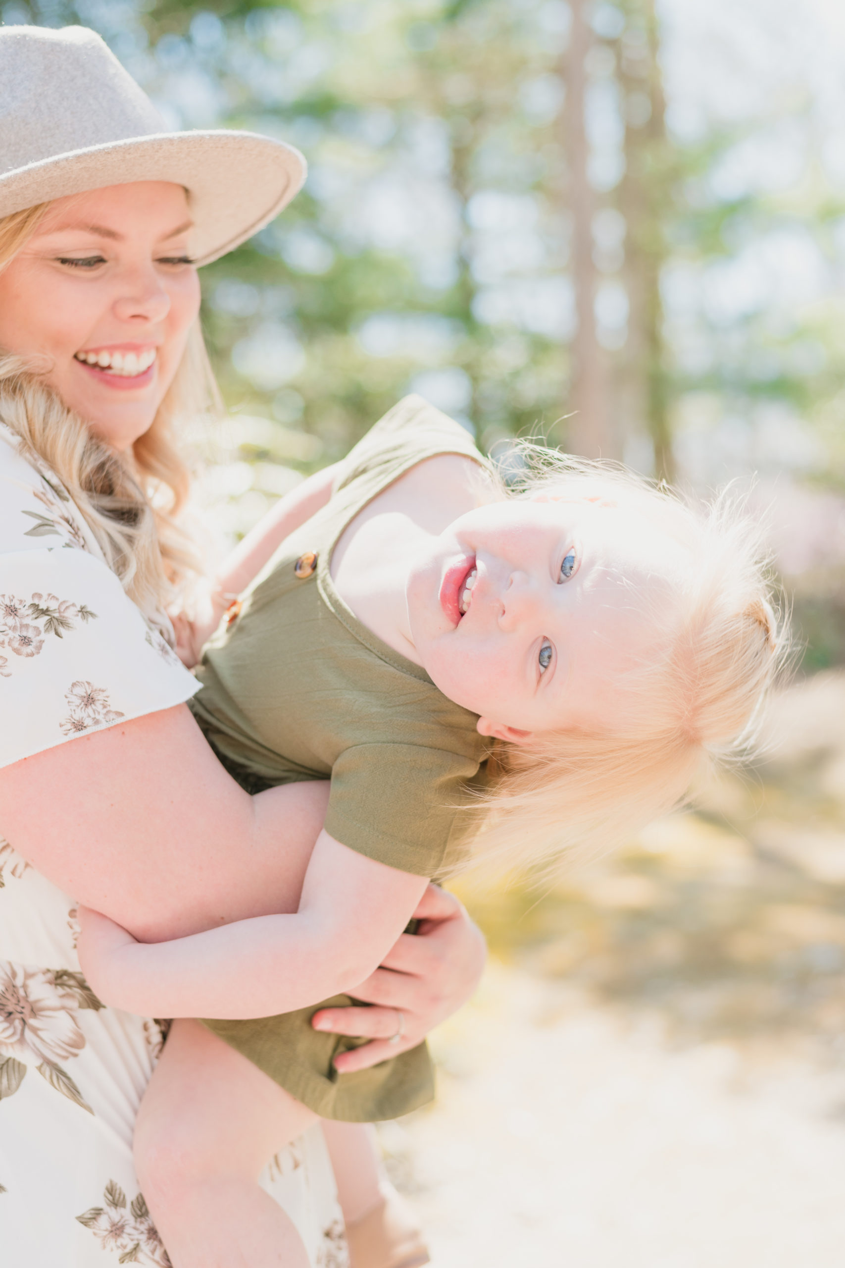 Mother holding young daughter. Daughter is leaning towards the camera and mother is smiling. The two are having fun twirling during mommy and me session at Spohr Gardens