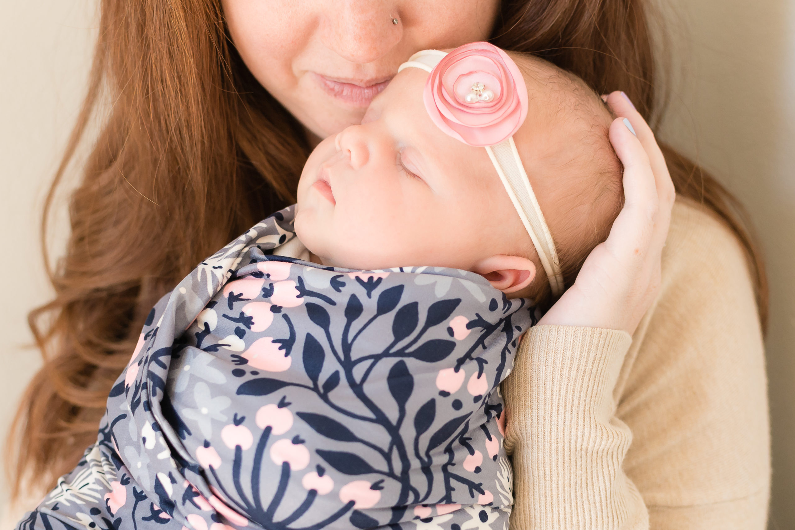 up close image of mother and newborn daughter during mommy and me lifestyle newborn session. mother is cradling newborn's head and snuggling into baby's temple. they are bathed in beautiful natural light