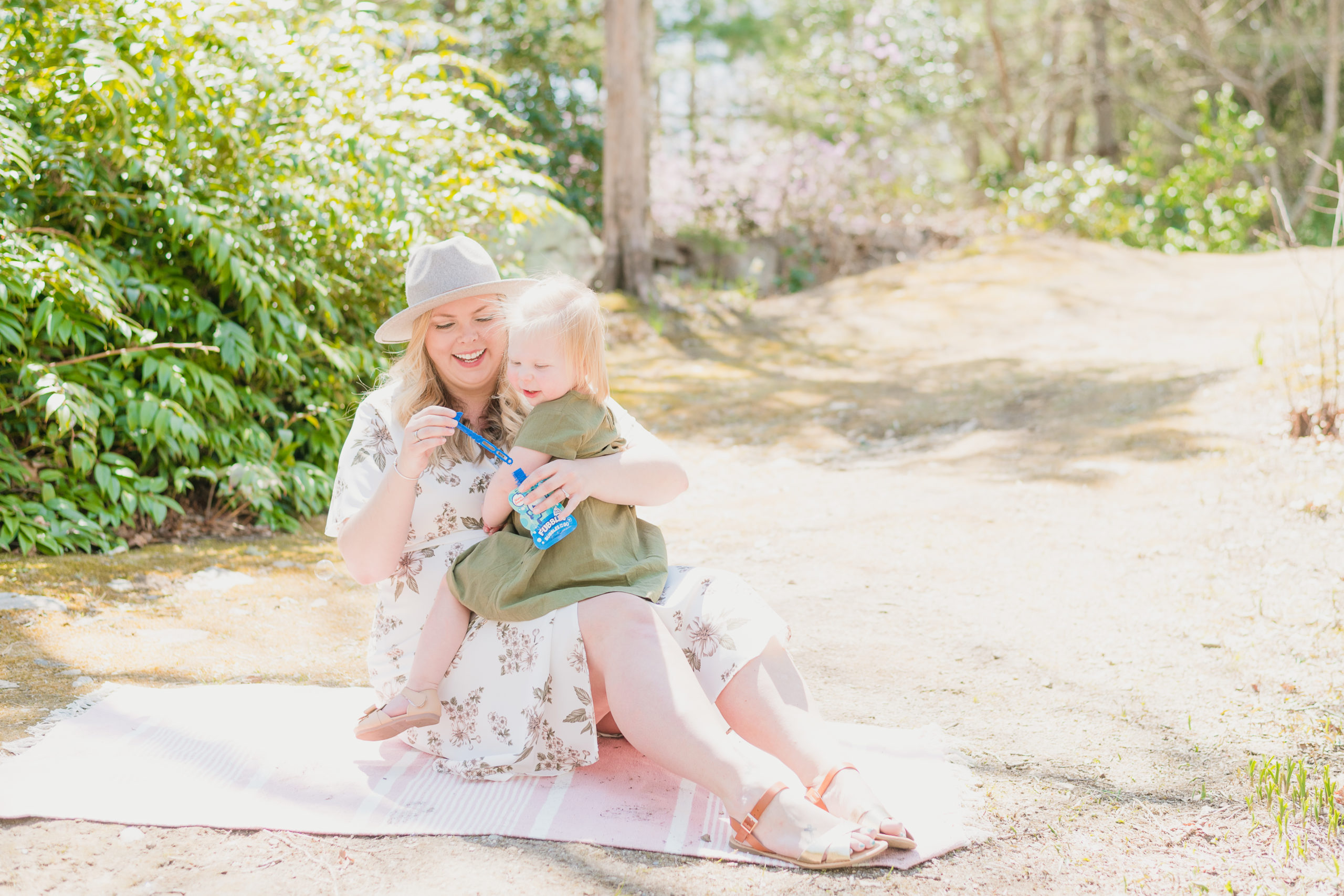 Mother and daughter sitting on the grounds of Spohr Gardens blowing bubbles during their mommy and me session.