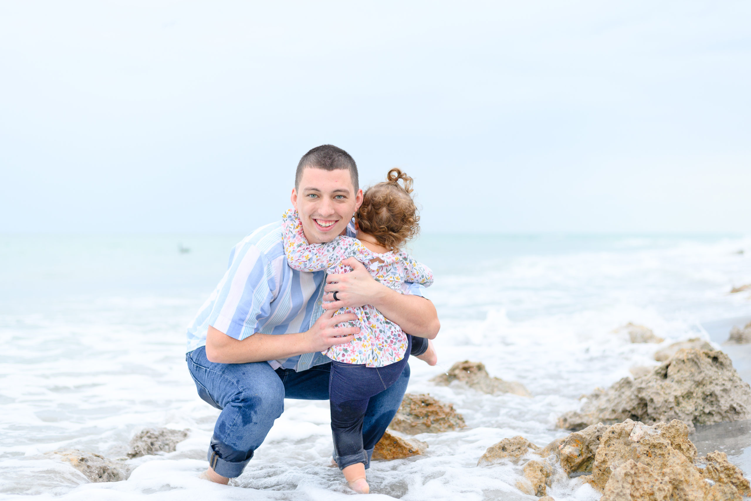 Father and daughter image. Father is hugging young daughter while she looks out at the water. They are both in the surf as the water comes lapping over the rocks. Taken during family beach session in Venice Beach