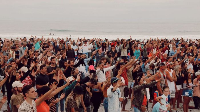 Image of crowd at Sean Feucht's worship event, hands raised, no masks