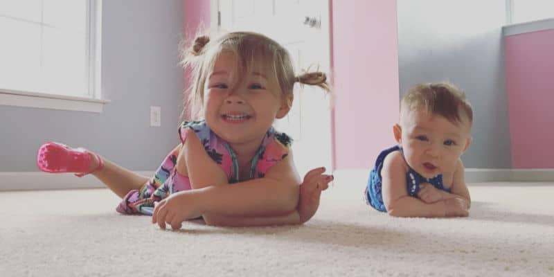 toddler and baby on the floor in the room they share before naps