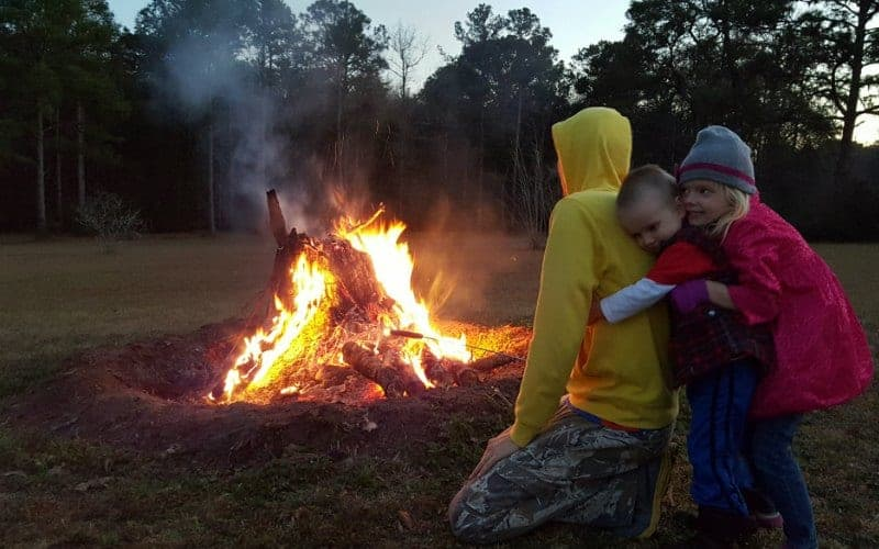 two kids hugging their dad outside at night by a fire