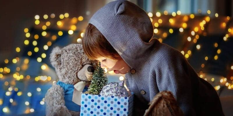 family Christmas traditions, child looking at present