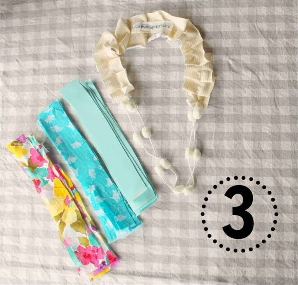Step 3 in the 15 minute DIY Birthday Girl necklace is to knot the fabric scraps on the bottom portion of the necklace, and then trim them as desired.