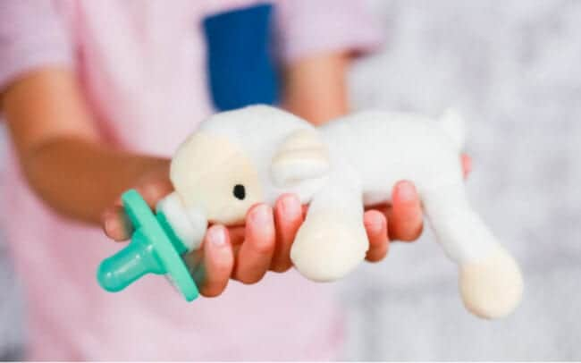 child holding pacifier with stuffed sheep attached