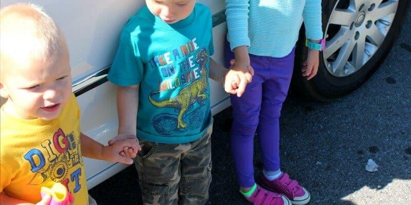 kids holding hands beside van