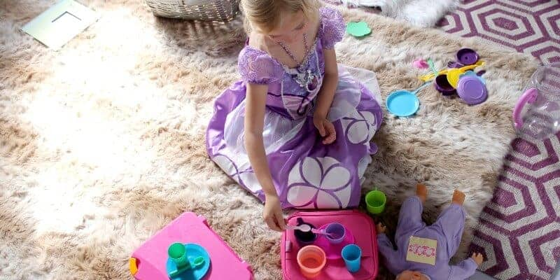 girl in princess dress having a tea party during independent play time