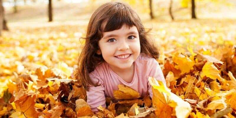 little girl smiling in a pile of leaves