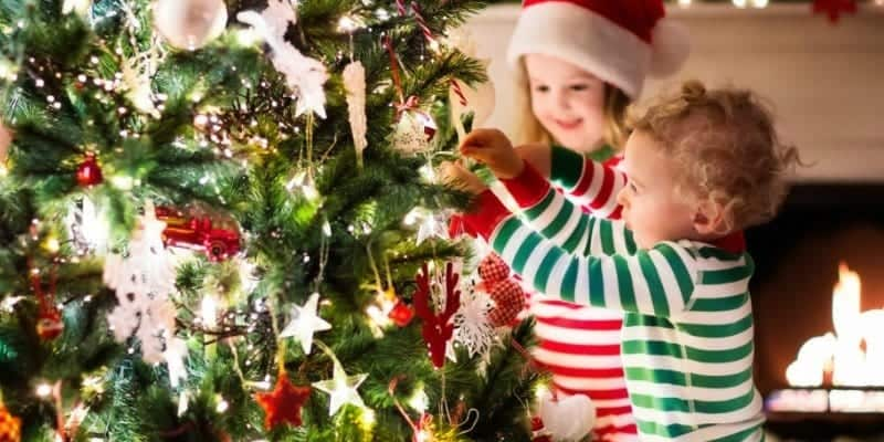 Kids are standing by Christmas tree on Christmas morning.