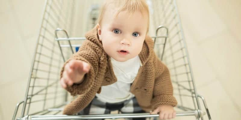 baby in a shopping cart being watched by daddy