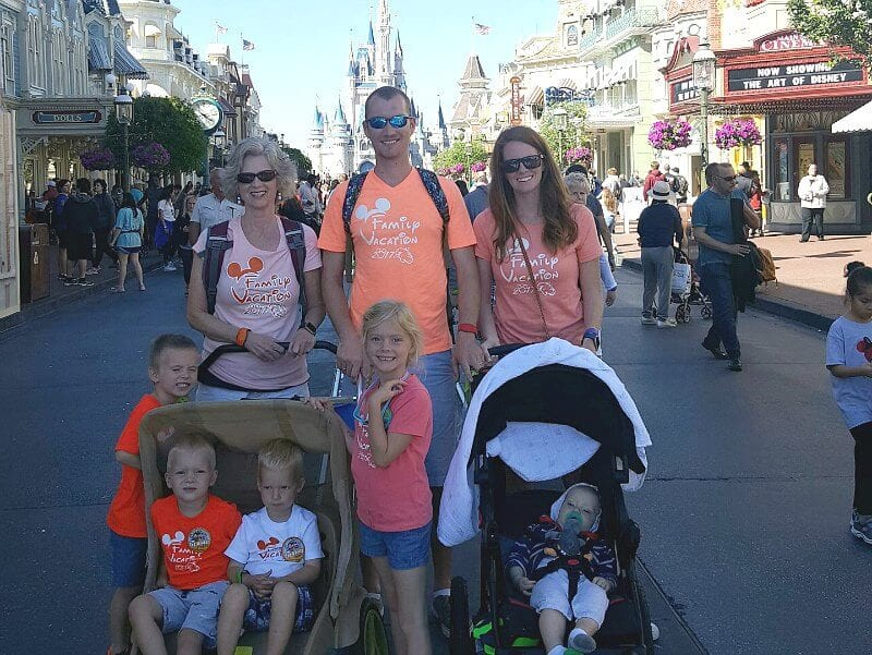 a family at disney world with strollers