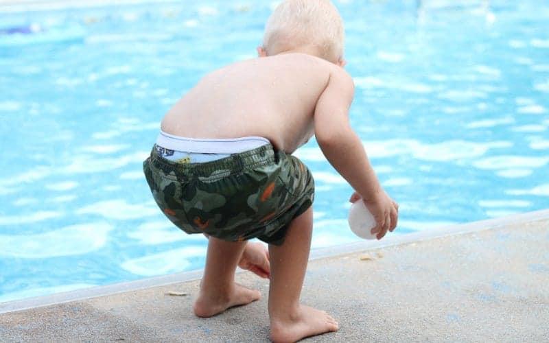 little boy by swimming pool