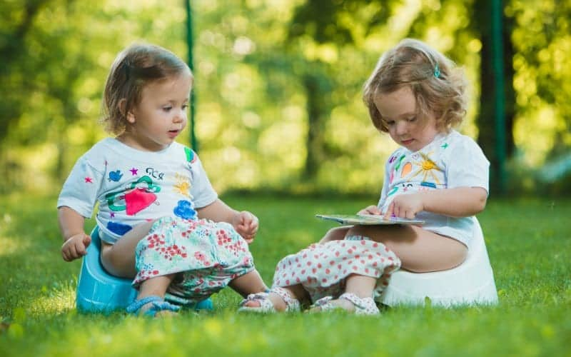 two toddlers getting potty trained sitting on the grass with potty training supplies