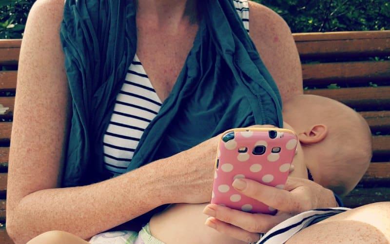 mom nursing baby while on phone