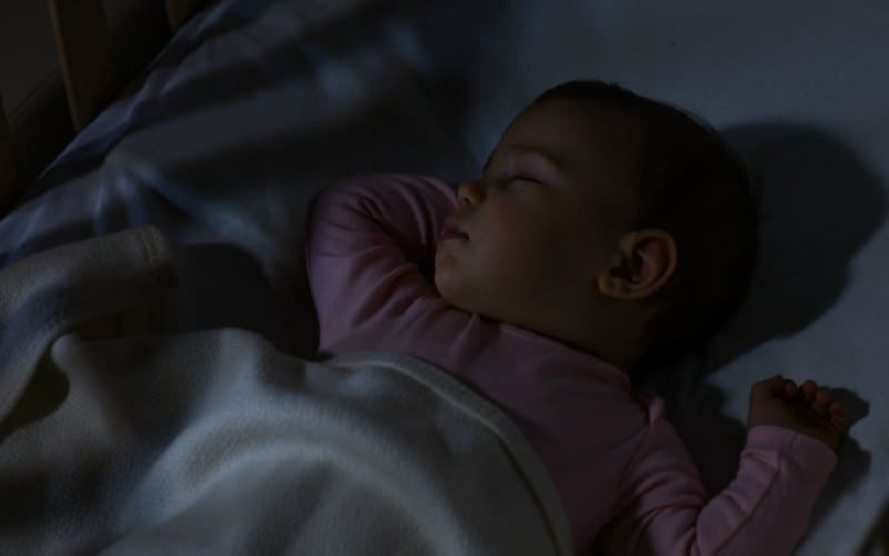 baby sleeping in darkness