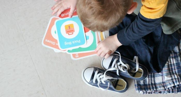 printable daily routine cards laying on floor with child looking at them