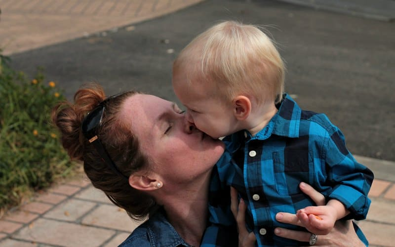 mom kissing baby boy who is not mom burnout