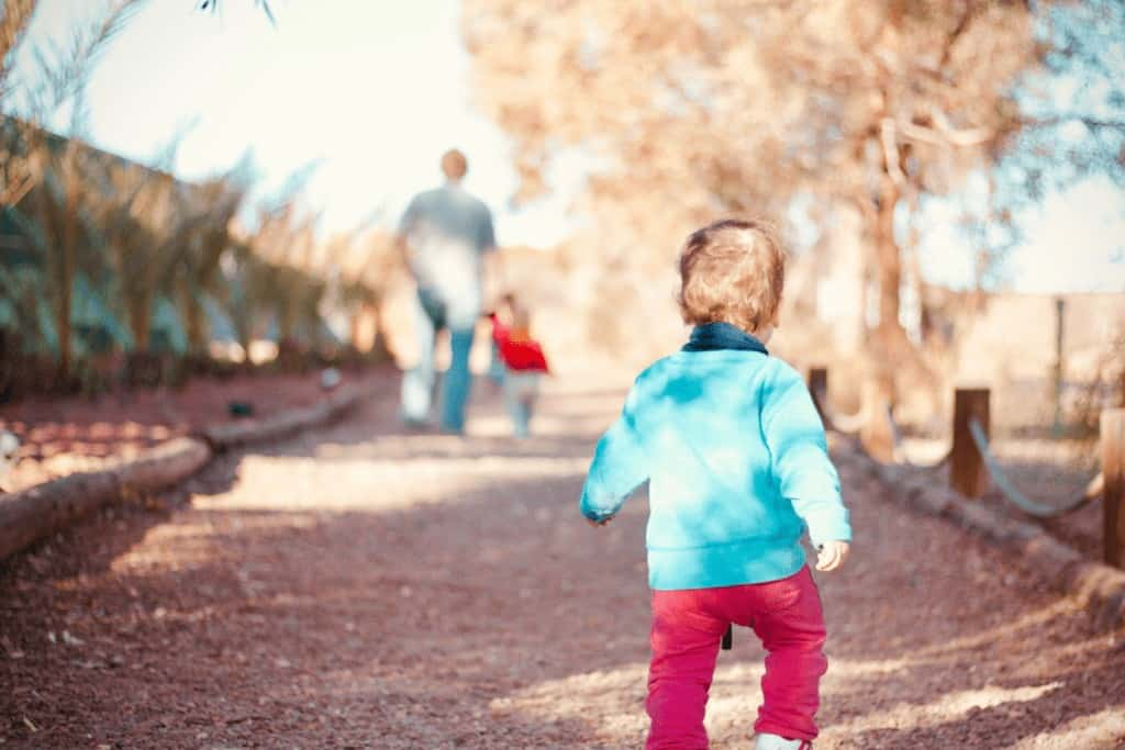 toddler running to catch up with dad at a park