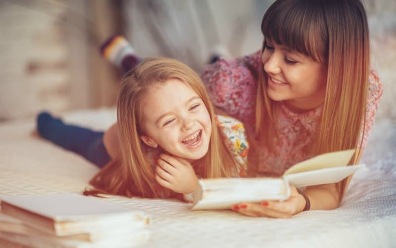 smiling mom and laughing daughter reading